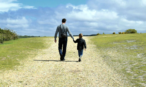 father and son walking across a field