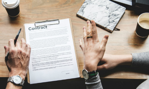 person holding pen in front of contract