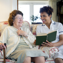 Older woman and caregiver reading together