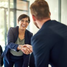 woman shaking man's hand in workplace setting